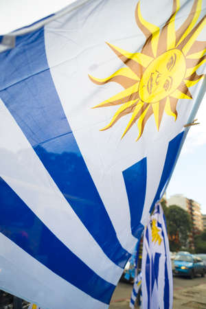 Uruguayan flag in Montevideo city street market background. Uruguay country national emblem.