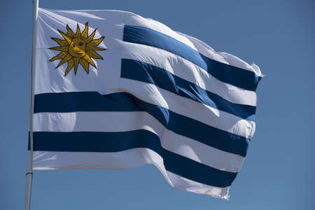 Uruguay country flag waving in the wind on blue sky background. National south american uruguayan emblem. Stock fotó