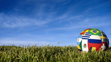 Soccer ball with international country flag of russian sport event groups. Realistic football on grass field over blue sky background. Includes russia, brazil, mexico and more.