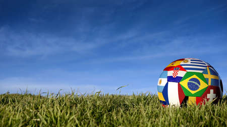 Soccer ball with international country flag of russian sport event groups. Realistic football on grass field over blue sky background. Includes brazil, france, mexico and more.