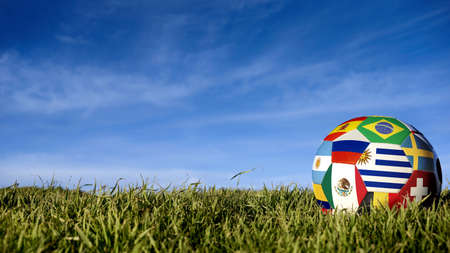 Soccer ball with international country flag of russian sport event groups. Realistic football on grass field over blue sky background. Includes uruguay, argentina, mexico and more.