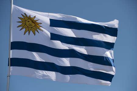 Drapeau uruguayen dans le vent sur fond de ciel bleu. Mât du pays de l'Uruguay avec emblème national.