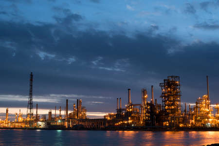 Industrial refinery at sunset with cloudy sky, petroleum factory buildings on water coast in dusk time. Stock Photo