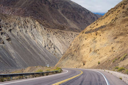 Mountain desert landscape with rocky hills and car driving lonely road of Argentina, south america.