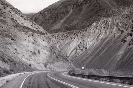 Mountain desert landscape with rocky hills and car driving lonely road of Argentina, south america in black and white.