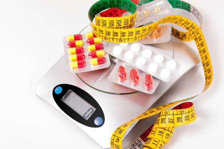 medicament: cinta m�trica y el medicamento sobre balanza de cocina