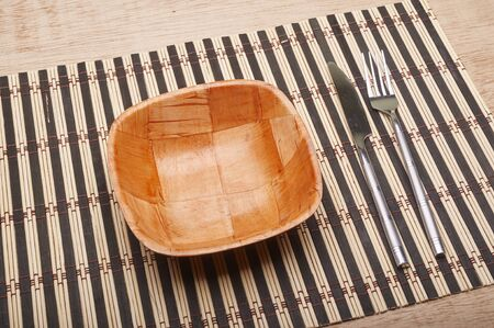 placemats: Bowl, fork, knife on placemats on dining table
