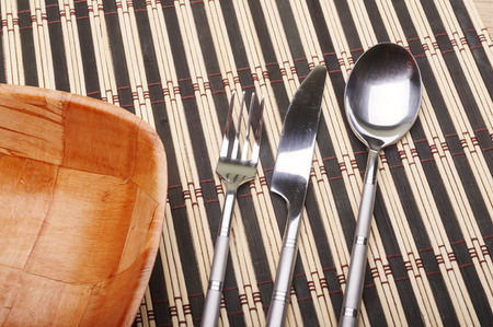 placemats: Bowl, fork, knife and spoon on placemats on dining table