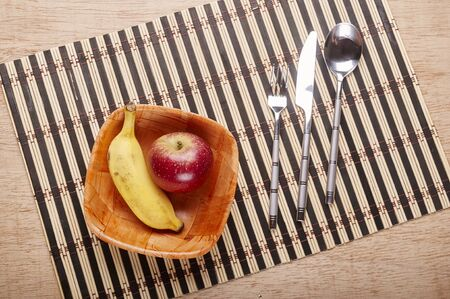 placemats: Bowl with banana and strawberry, cutlery and placemats on dining table