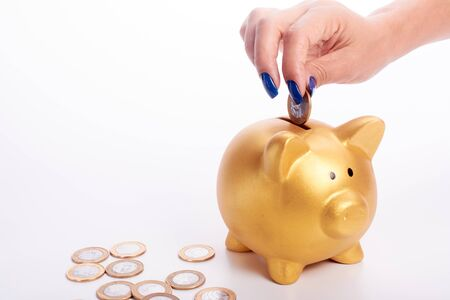 piggy: Womans hand putting coins of the Brazilian money into piggy bank in white bakcground. Stock Photo