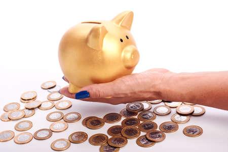 banco dinero: banco de mano de la mujer que sostiene la batería y monedas del dinero brasileño dispersos en el fondo blanco.