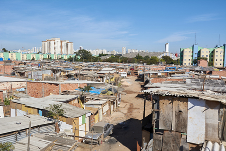 financed: Slum and building popular in Sao Paulo. Illegal and fragile constructions near housing financed by the government for the poorest people. Stock Photo
