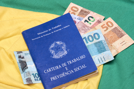 Brazilian work books or document work, social security or worker rights (Carteira de trabalho e Previdencia Social) on the Brazilian flag with money notes.