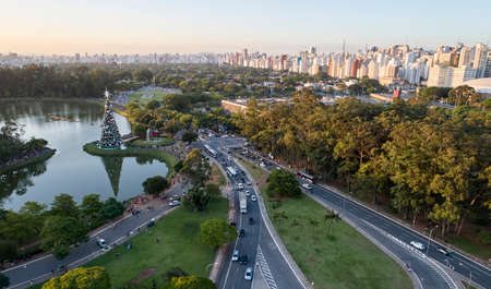 Aerial view of Sao Paulo city and traditional Christmas tree in Ibirapuera Park. Environmental preservation area with trees and green area at Ibirapuera Park in the city of Sao Paulo, Brazil.