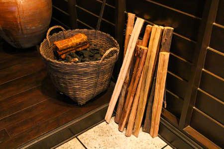 log basket: Wood basket carries a burned log