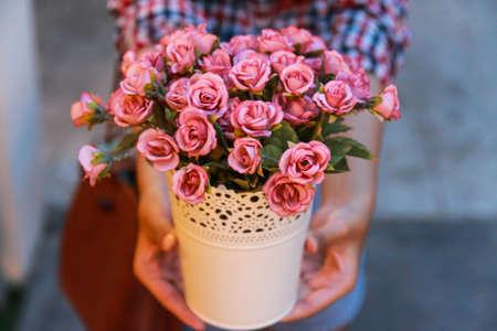 jardines con flores: mano que sostiene rosas de color rosa en una olla