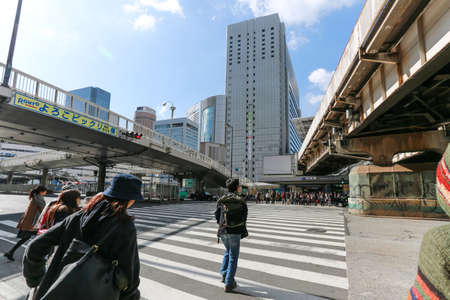febuary: OSAKA - FEBUARY 9: People walk across the street at Osaka station on fEBUARY 9 2015 in Osaka. It is a city in the Kansai region of Japans main island of Honshu