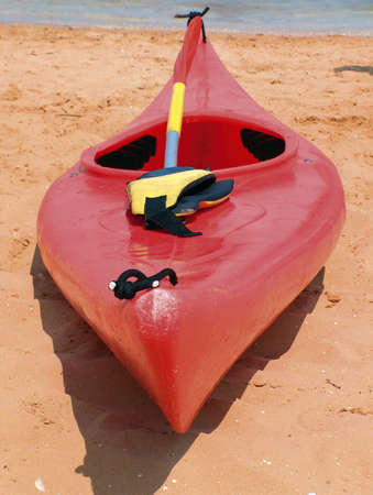 red plastic canoe on a beach Stock Photo - 330080