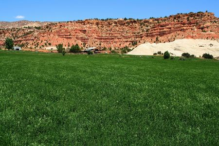 View of a farm in the  desert with hay in the foreground and a red rock mountain  in the background with blue sky's