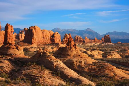 View of the red rock formations in Arches National Park with blue sky�s and clouds  photo