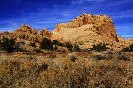 View of red rock formations in San Rafael Swell with blue sky's the and clouds
