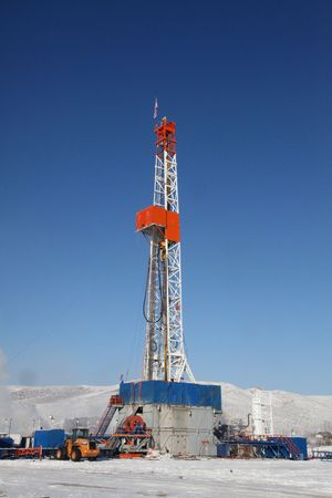 oilfield: Drill Rig with blue sky and snow