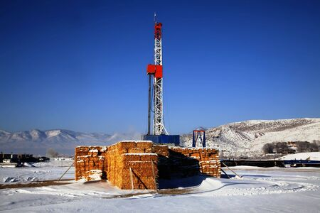 Drill rig with snow on the ground with blue sky Stock Photo