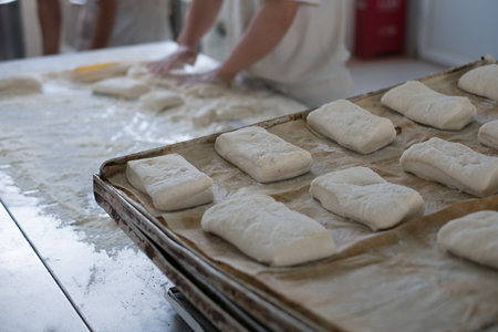 A baker with hands in flour prepping fresh ciabatta bread rolls that show in the forground.