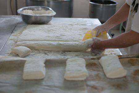 A baker cutting freshly made bread dough on a tray showing raw Ciabatta bread ready to be baked.