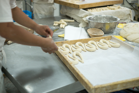 bowel: Bakers working on making fresh pretzel dough on a table covered in trays, dough, mizing bowel and yellow dough slicers.