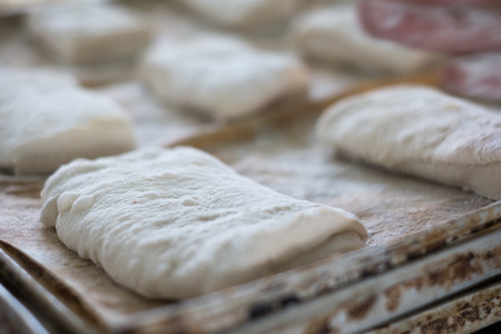 A close up shot of uncooked raw Ciabatta bread Rolls sitting on a metal tray waiting to be baked.