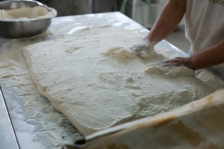 french boule: Action shot of baker spreading flour on a flat of Ciabatta bread. Flour is toss along the side as he prepares to cute the Ciabatta dough into individual rolls.