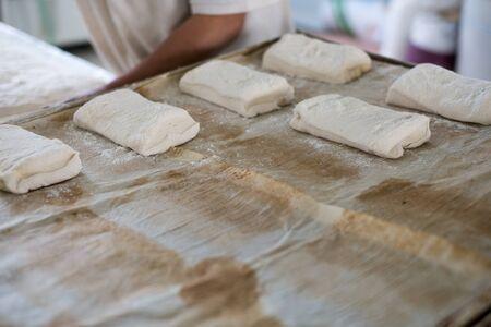 A bakery placing freshly prepped raw ciabatta bread roll on a tray.