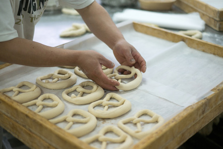 french bread boule: A bakery placing a mirrored pretzel on a wooden tray on a prep table within a bakery.