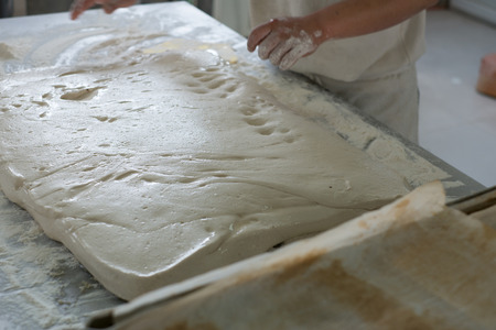 A baker prepping a flat of raw ciabatta bread for flouring and baking. Stock Photo