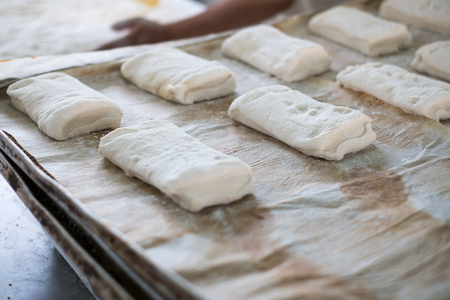 A blurred out baker prepping fresh ciabatta Rolls on a wax paper sheet and metal tray. Stock Photo