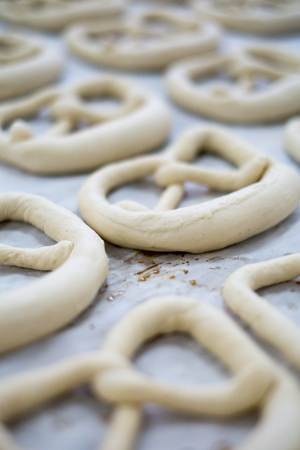 Fresh Pretzel Dough on a bakers sheet sitting on wax paper. Raw uncooked but looking delicious as a mirrored brezel or Breze.