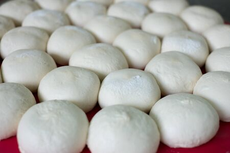 Round tray of ready to bake bread dough to be baked into bread buns or bread rolls.