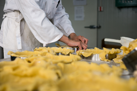 PrEP: A pastry chef using two hands to prep pie dough or pie crusts for baking at a local bakery. Stock Photo