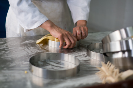 PrEP: Pastry chefs hands pulling pit dough into a stainless steel pie crust ring sitting on flour dust covered stainless steel prep table.