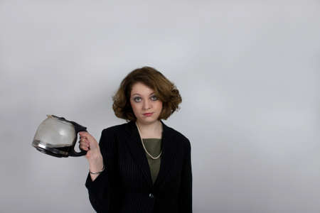 Young woman snarling as she holds coffee pot photo