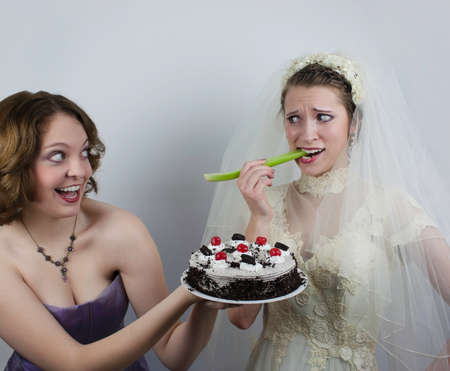 A bridesmaid holds a cake and tries to tempt a bride that is eating a piece of celery  Stock Photo