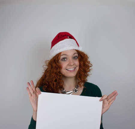 Young woman wearing Santa hat holding empty sign photo