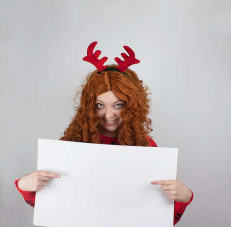 Pretty young woman wearing antlers and holding blank sign photo