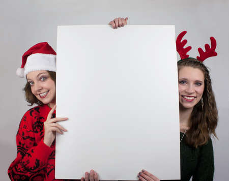 Two young women wearing Santa hats and antlers and holding blank sign photo