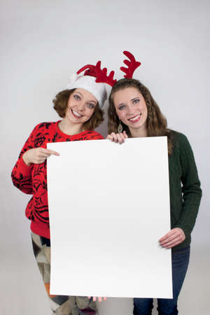 Two young women wearing Santa hats and antlers holding blank sign photo