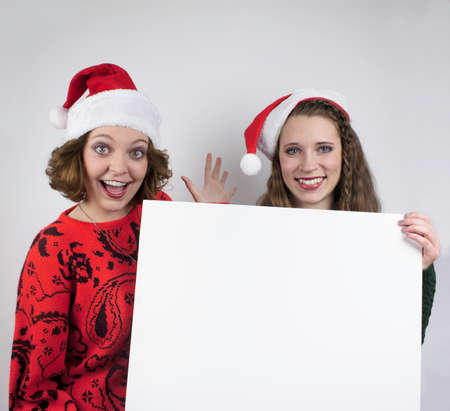 Two young women wearing Santa hats and holding blank sign photo