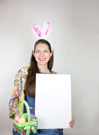Young woman wearing rabbit ears and holding an Easter basket and blank sign for copy space photo