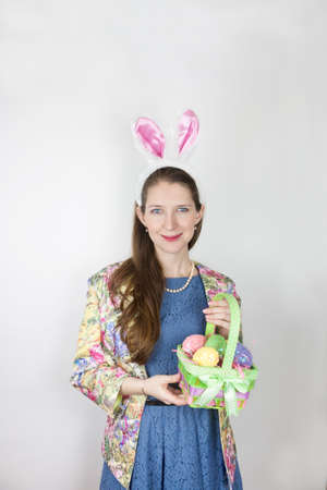 Young woman wearing rabbit ears and holding an Easter basket photo