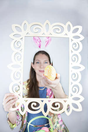 Young woman wearing rabbit ears and holding yellow sequin Easter egg out of picture frame photo